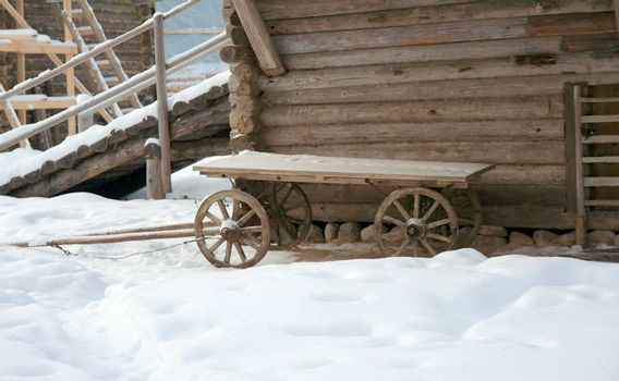 Wooden cart near the peasant's house in winter. Modern reconstruction of Russian peasant life of the beginning of XX century