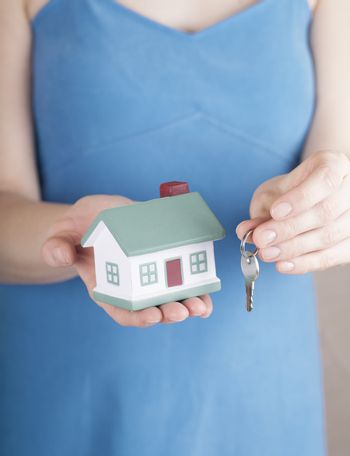 Woman in blue dress offers house toy and keys