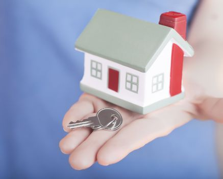 Little house toy and key in woman's hand