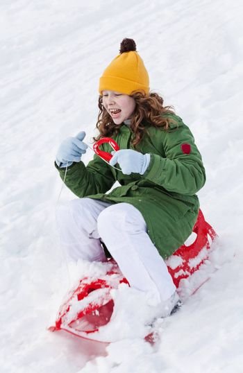 Girl slides down hill on red plastic sledge in a snowy winter park
