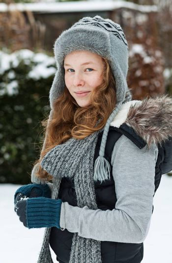 Outdoor portrait of a cheerful teenager girl in winter cloths