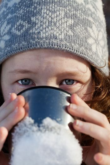 closeup portrait of teenagergirl in winter hat drinking from flask cup