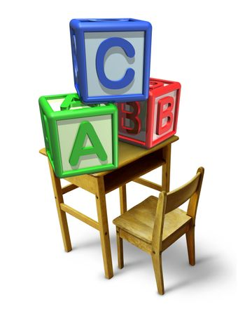 Primary education and early childhood learning with a school desk and basic letter blocks with a b and c representing childcare training of reading and writing skills.
