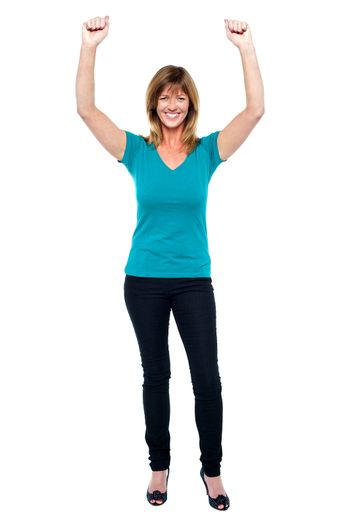 Joyous middle aged blonde celebrating her success. Throwing her hands up in the air.