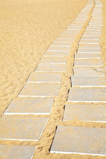 Generic Vertical take of stone flags laid to form a path from a parking lot to a beach over the hot mid day sand