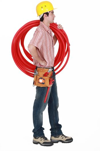 Plumber carrying spool of piping