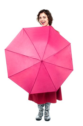 Cheerful woman being playful with umbrella