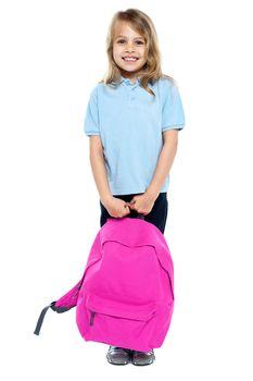 Little schoolgirl posing with pink backpack