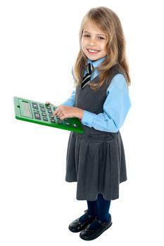Schoolkid pressing key 5 on big green calculator