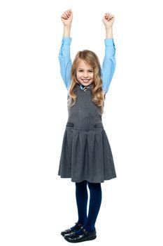 Cheerful kid raising her hands in excitement