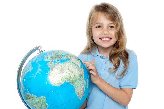 Young girl selecting holiday destination over globe