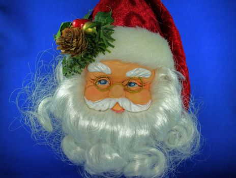 Close up of decoration of Santa Claus face with glasses on blue background