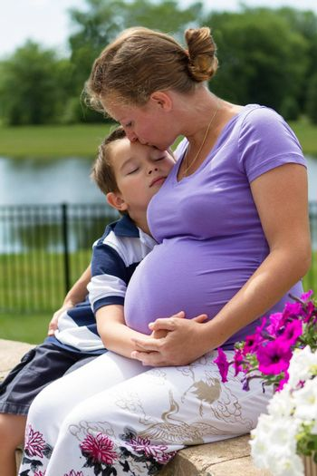 Pregnant woman holding her belly with her son while kissing him.