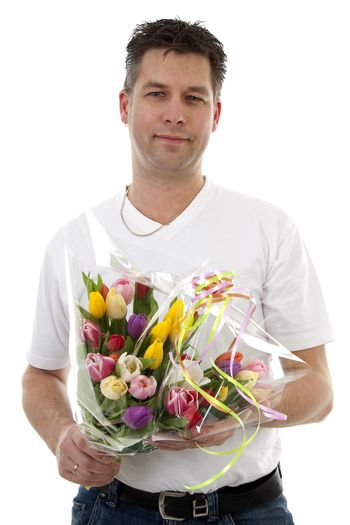 Young man is giving bouquet of colorful tulips over white background