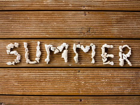 Wooden planks decorated with text summer, engraved with pebbles.