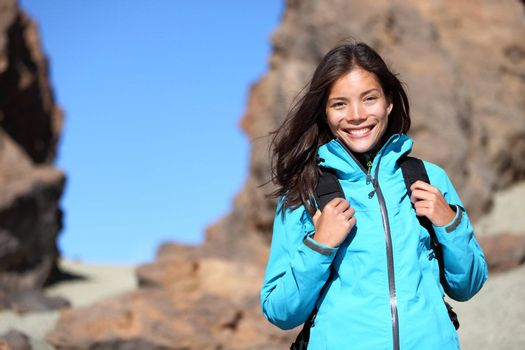 People hiking. Hiker woman looking at camera smiling happy portrait. Multicultural young woman walking in mountains with backpack