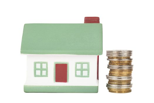 Little house toy and stack of coins isolated over white background
