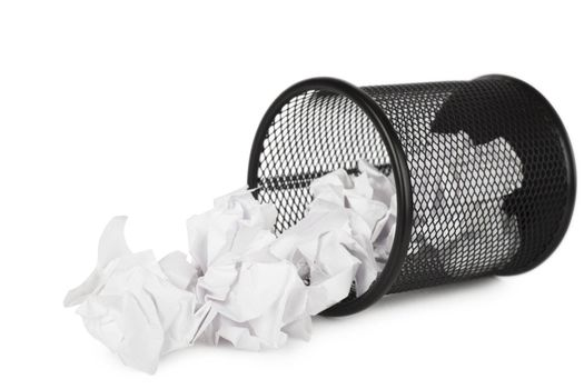 Trash can filled with crumbled paper canted on a side isolated on white background