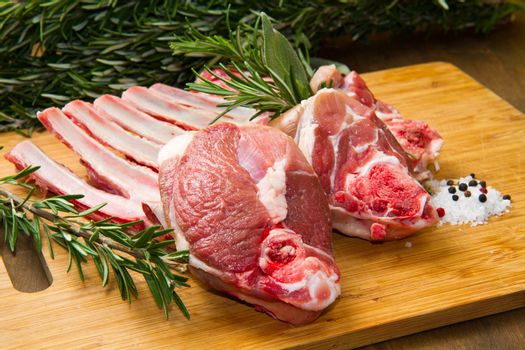 a group of rib lamb with oil and rosemary on wood table