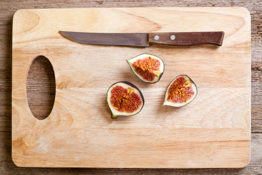 figs and old knife on wooden board