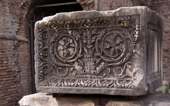 A stone block carved with a floral decoration created by the Roman Empire.  The block is located in the Roman Forum in Rome, Italy.