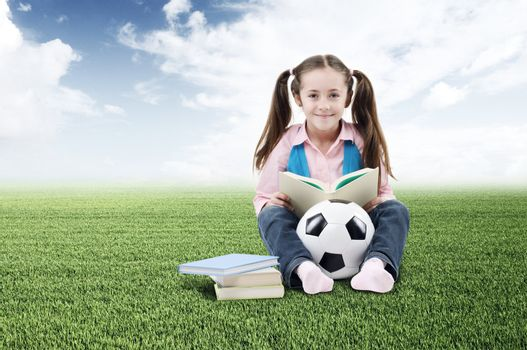 Cute little girl with books and soccer ball on green grass