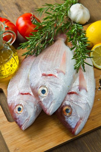 a group of sea bream with lemon and rosemary on wood table