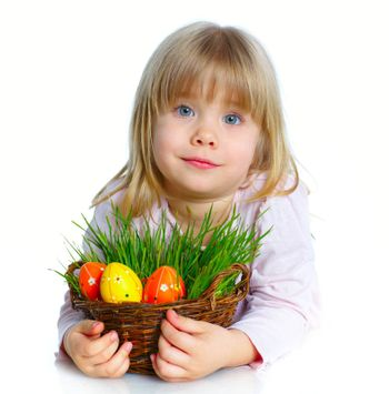 Adorable little girl collecting Easter eggs and grass in her basket
