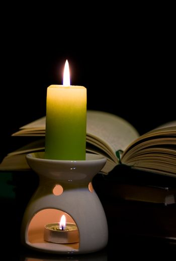 Candle and book on dark background