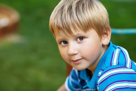 Horizontal outdoor portrait of a cute blond boy