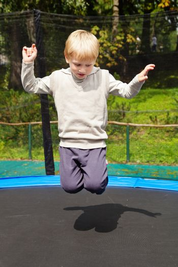 Blond boy jumping on trampolin at an outdoor playground