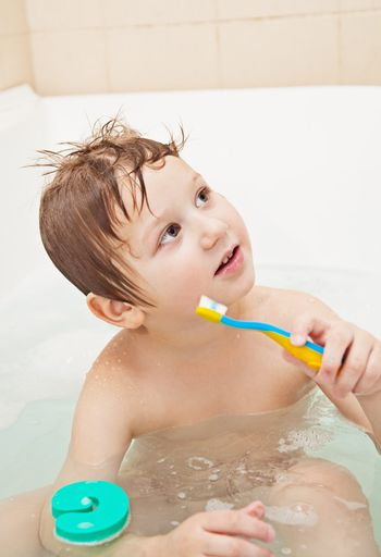 Cute little boy sitting in the full bath and holding toothbrush