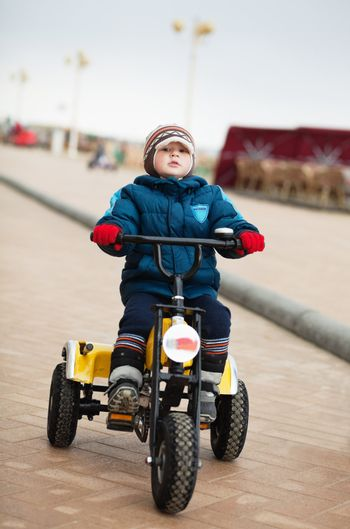 Little boy riding tricycle in a cold winter day
