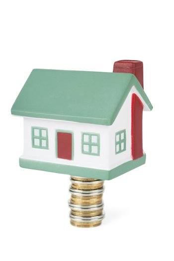 Little house toy on a stack of coins isolated over white background