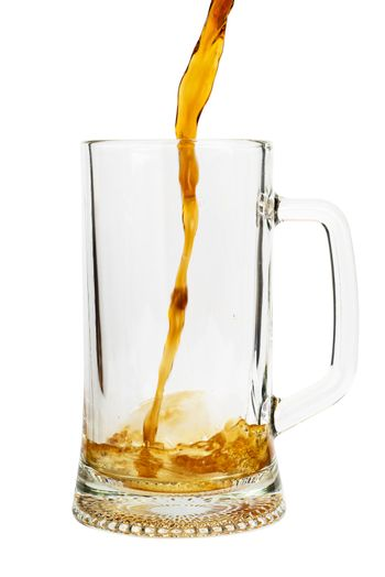Beer pouring into glass isolated over white background