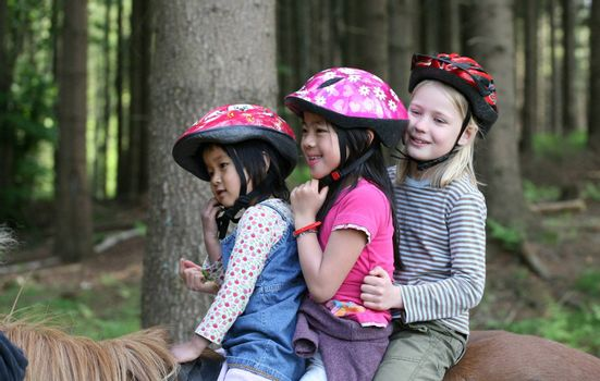 three friends:  one caucasian blond and two  asian (9 years +5 years) on horses in a forest