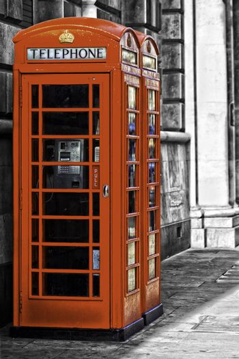 Two iconic red British telephone booths on an urban street with coin-operated payphones for public convenience