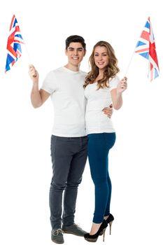 Cheerful couple waving the British flag