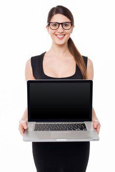 Pretty girl presenting brand new laptop