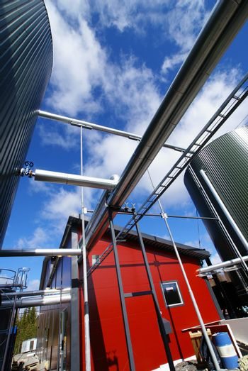 industrial piping and tanks against blue sky