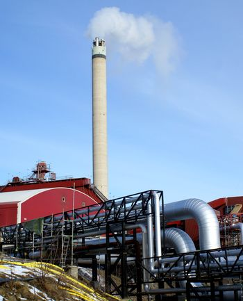Industrial zone, Steel pipelines and smokestack against blue sky