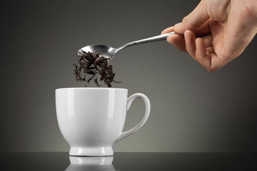 tea pour out into white cup on grey