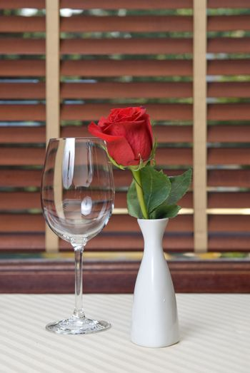 wineglass and rose on the table