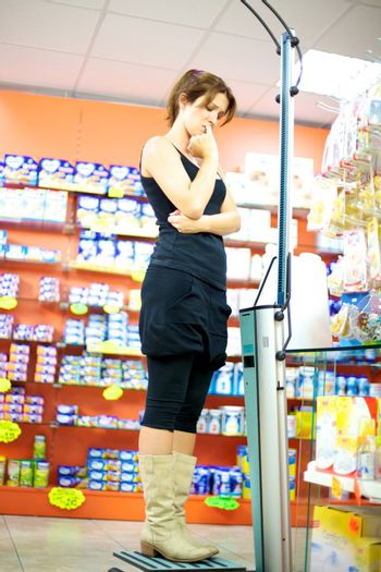 Woman in pharmacy stressing standing on balance