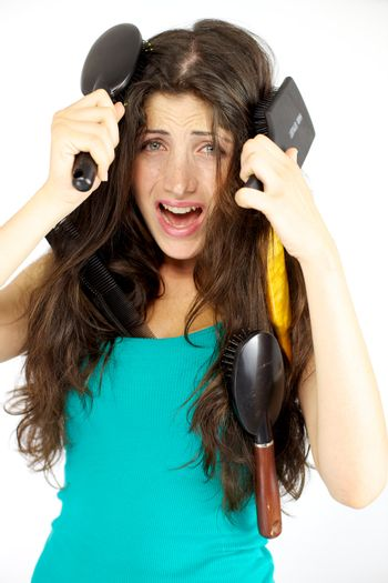 Unhappy young woman with hair tangled in many brushes not able to brush herself