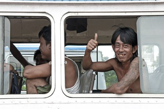 man smiling on yangon myanmar bus