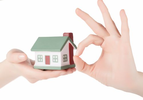 Little house toy in woman hands isolated over white background