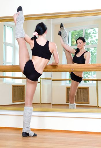 Portrait of young sporty girl doing physical exercise in front of mirror