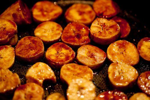 bananas in the pan in boiling caramel