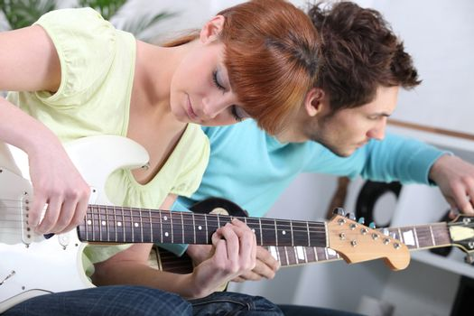 Young couple tuning and playing guitar
